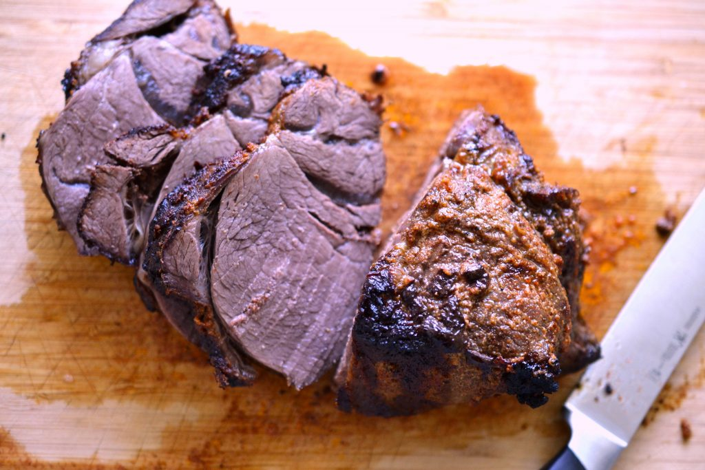 Bison top sirloin roast sliced on cutting board