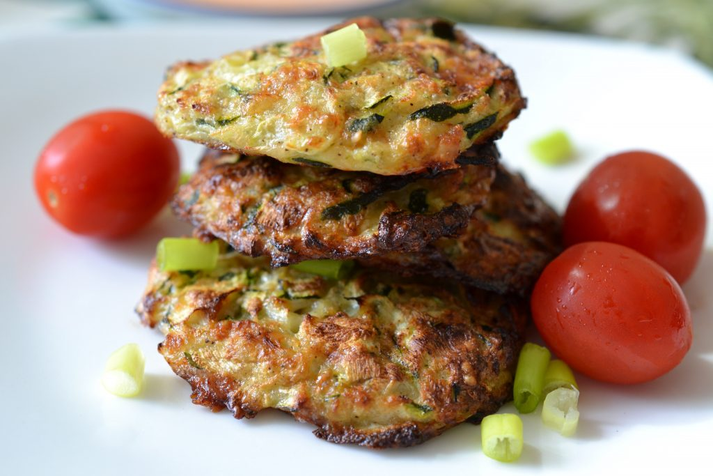 Stack of zucchini fritters on a plate with grape tomatoes