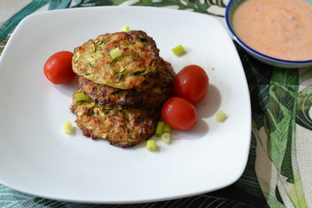 Zucchini fritters on a plate next to small dish of sauce