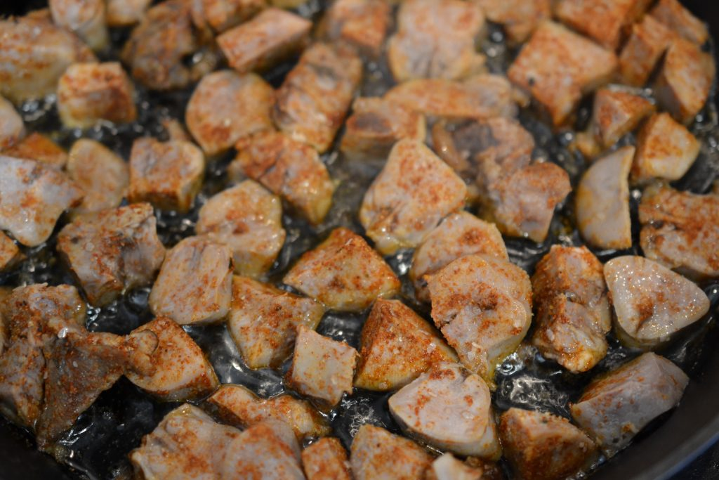 Lamb tongue cubes being fried in a cast-iron pan.