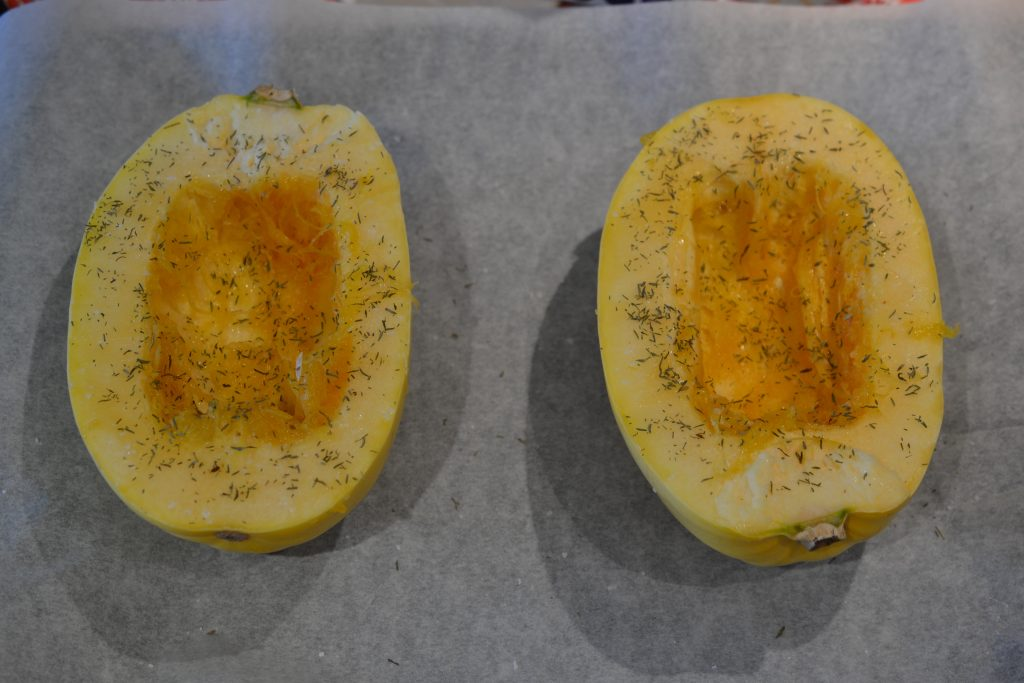 Spaghetti squash on a baking sheet before roasting in the oven.