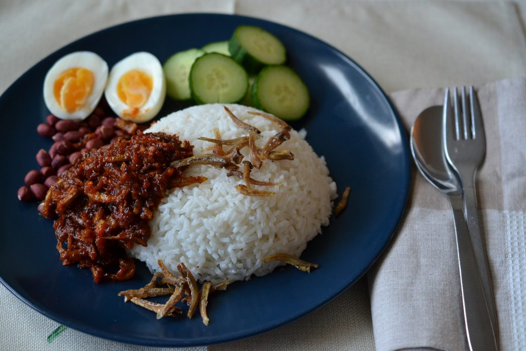 Nasi lemak on plate with a fork and knife next to it.