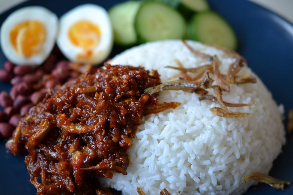 Close up of nasi lemak on a plate with fried anchovies, cucumber slices, boiled egg and ground nuts.