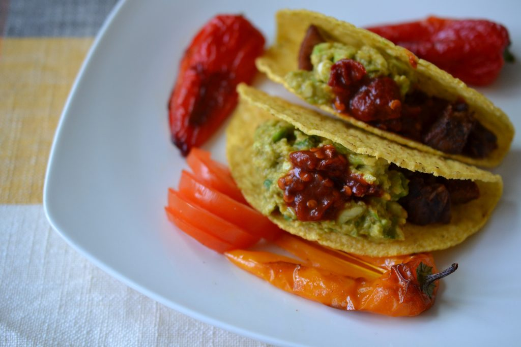 Lamb tongue tacos topped with guacamole, chipotle peppers, and roasted bell peppers.