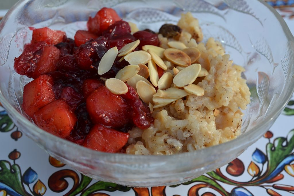 Rice pudding in a bowl topped with almonds and cranberry apple topping.