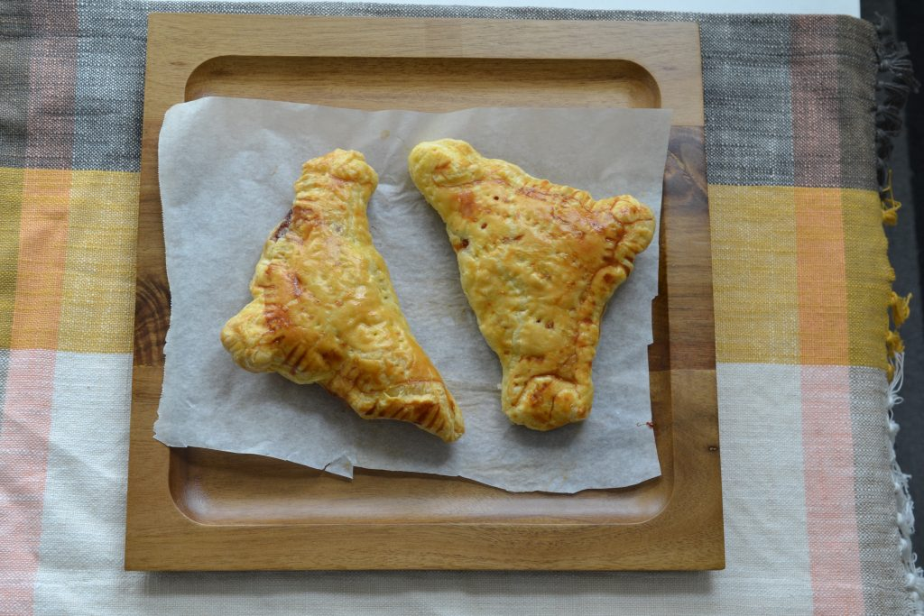 Two marmite and cheddar turnovers in a wooden tray.