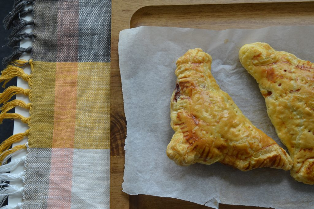 Two marmite and cheddar puff pastry turnovers on a tray.