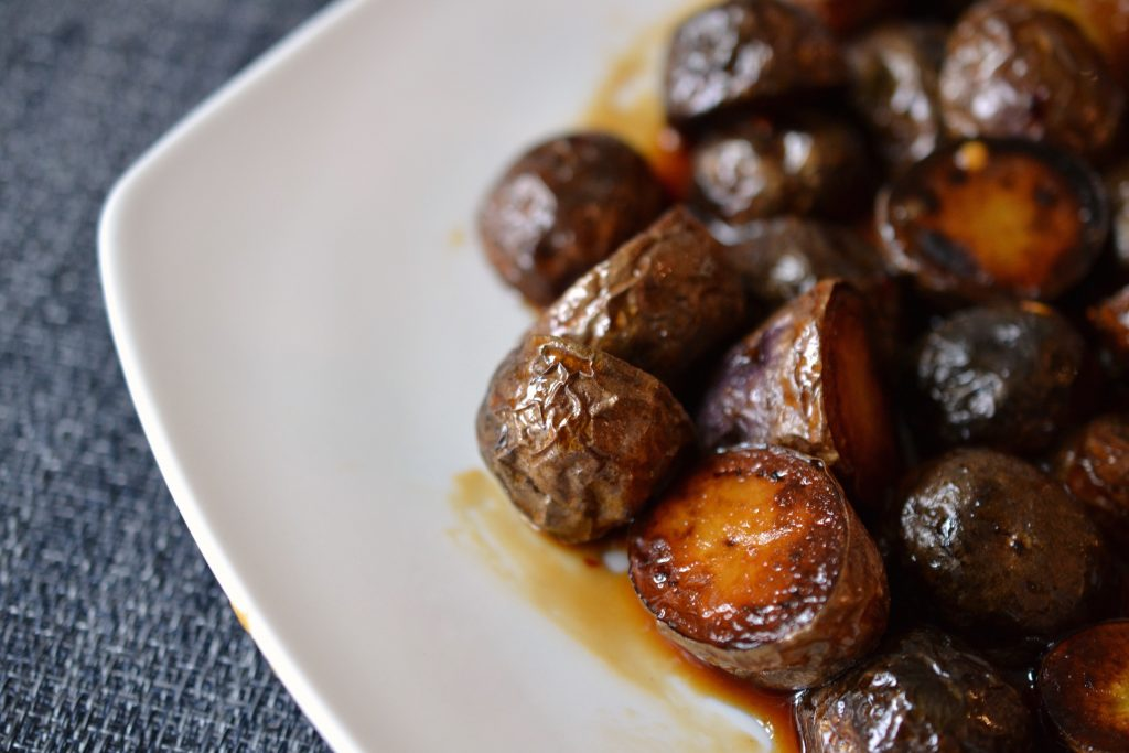 Honey and soy glazed potatoes on a plate.
