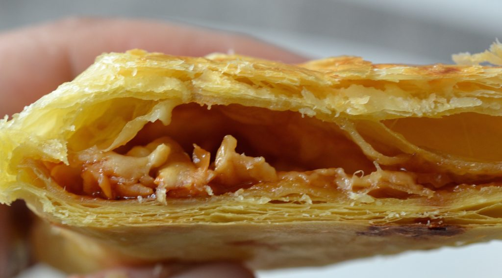 Cross section of marmite and cheddar puff pastry turnover, showing layers of melted cheddar, marmite and flaky puff pastry.