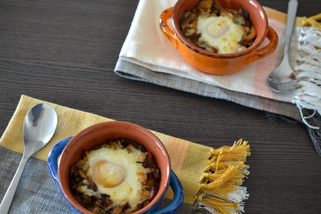 Two ramekins of baked eggs with mushrooms from above.