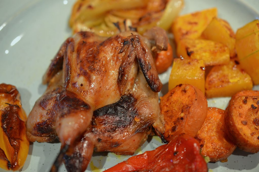 Broiled quail with roasted vegetables.