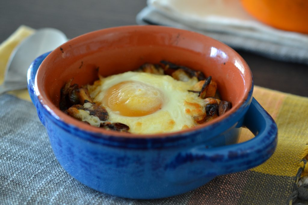 Close up of blue ramekin with baked egg with mushrooms.