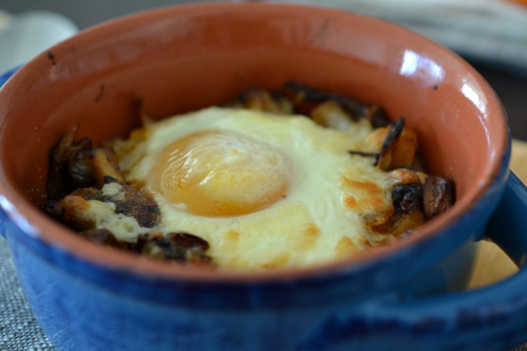 Extreme close up of baked egg with mushrooms, onions and peppers.