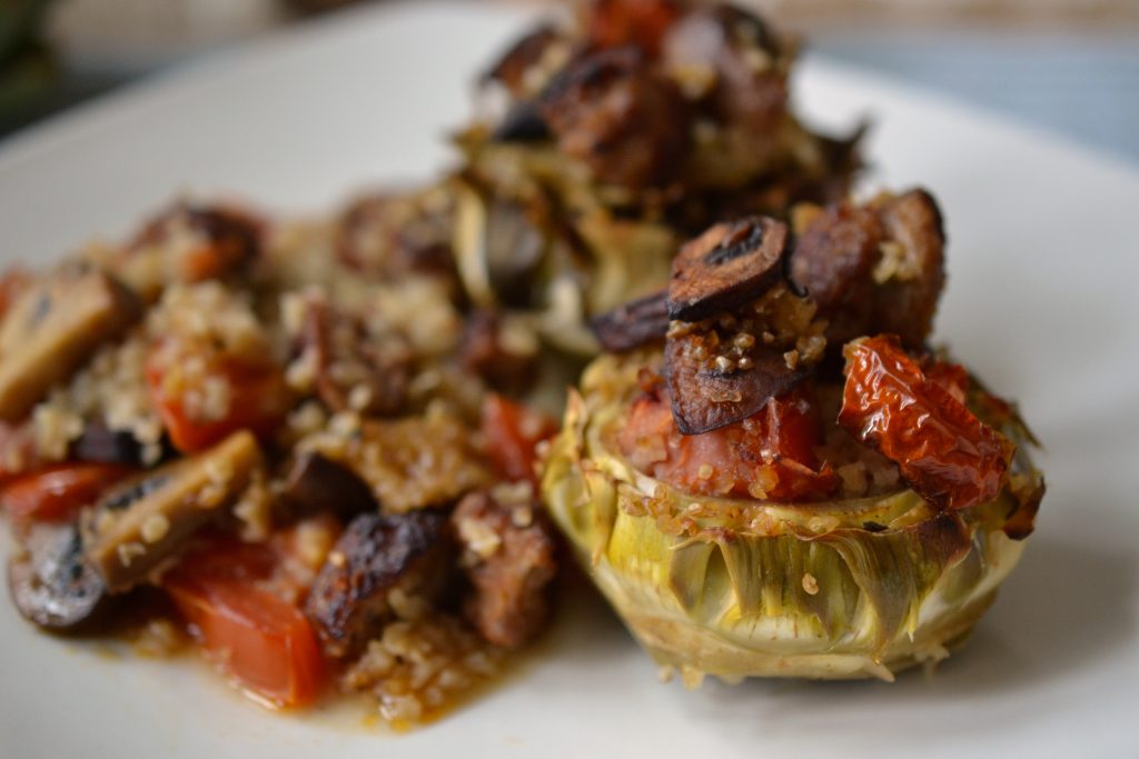 Stuffed artichokes with mushroom and sausages on a plate